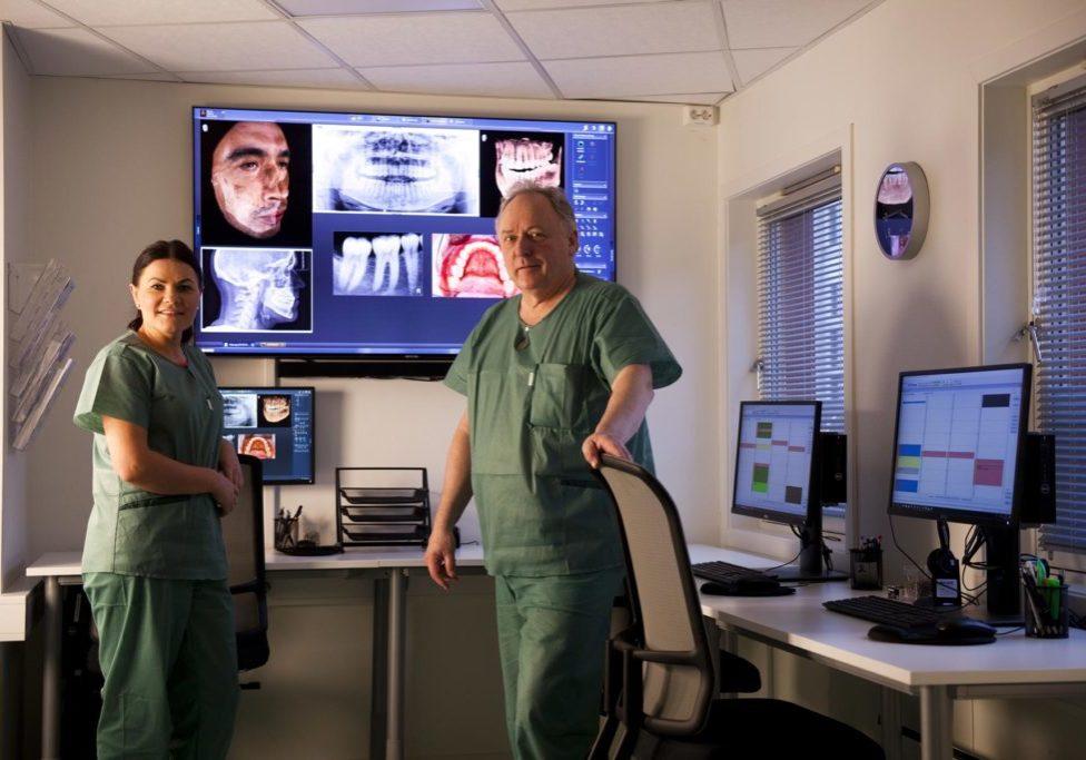 Kontrollrommet hos Tromsø Tannkirurgi og narkosesenter er godt utstyrt slik at ekspertene kan forberede seg godt før hver behandling. På bildet ser du en storskjerm, tre vanlige dataskjermer og to personer som studerer ulike bilder - både rødtgen og vanlige bilder.